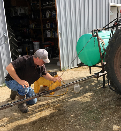 Flying AJ Ranch's Arlin preparing the tractor for a spraying run